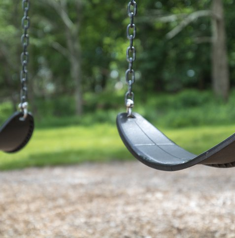 An empty pair of swings hang at the playground.